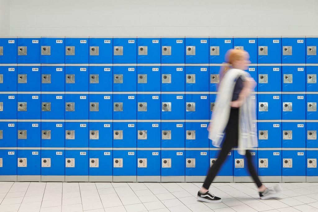 Girl walking past bank of lockers